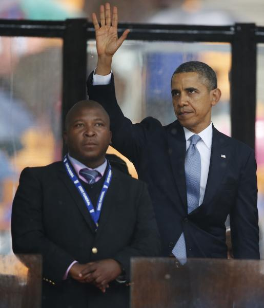 President Barack Obama waves standing next to the sign language interpreter after making his speech at the memorial service for former South African president Nelson Mandela at the FNB Stadium in Soweto near Johannesburg, Tuesday, Dec. 10, 2013. South Africa's deaf federation said on Wednesday that the interpreter on stage for Mandela memorial was a 'fake', (AP Photo/Matt Dunham)