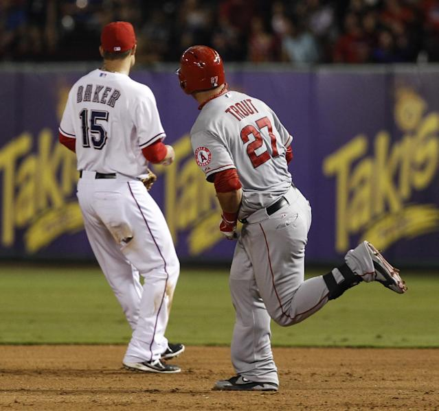 Los Angeles Angels' Mike Trout (27) rounds first base on his way to a double behind Texas Rangers first baseman Jeff Baker (15) during the fifth inning of a baseball game, Tuesday, July 30, 2013, in Arlington, Texas. (AP Photo/Jim Cowsert)