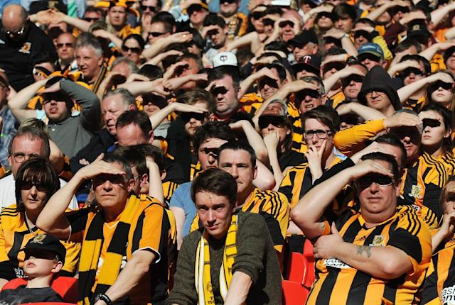 Hull City fans shield from the sun as they watch the English FA Cup semifinal soccer match between Hull City and Sheffield United at Wembley Stadium, London, England, Sunday, April 13, 2014. (AP Photo/Rui Vieira)