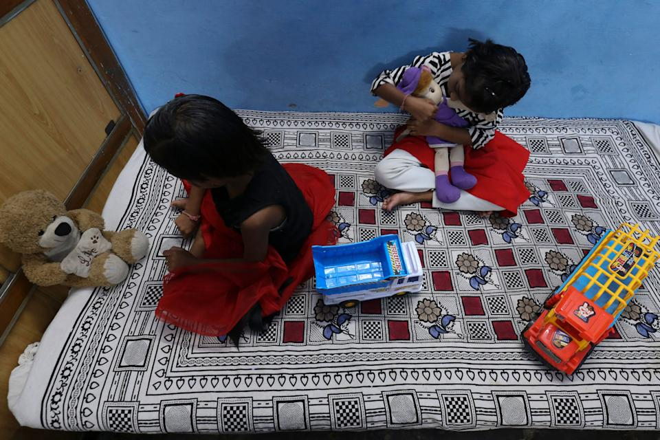In this picture taken on May 11, 2021, twin sisters Tripti and Pari, who lost both their parents due to the Covid-19 coronavirus, play with their toys at a relative's home in Bhopal. - Thousands of children have lost at least one parent in the new pandemic wave ravaging India, where there were already millions of orphans. - TO GO WITH AFP STORY children-health-India-coronavirus by Aishwarya KUMAR (Photo by Gagan NAYAR / AFP) / TO GO WITH AFP STORY children-health-India-coronavirus by Aishwarya KUMAR (Photo by GAGAN NAYAR/AFP via Getty Images)