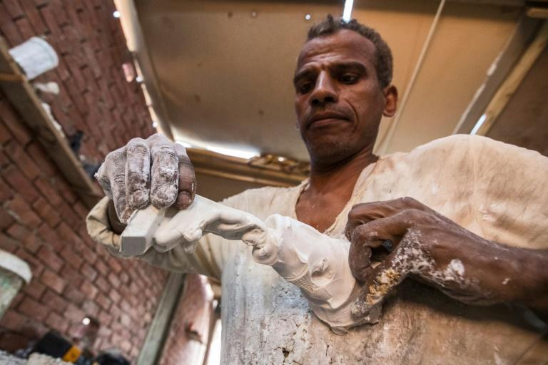 A craftsman shapes a moulded replica of an Ancient Egyptian bust figurine at a workshop in the district of Nazlet el-Semman near the Giza Pyramids Necropolis in Cairo