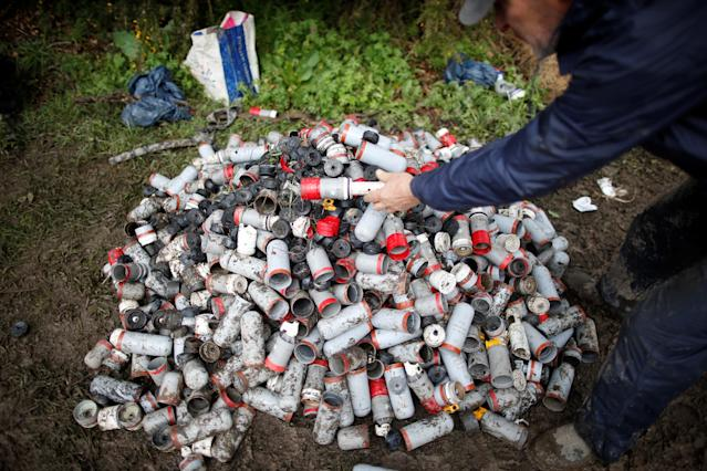 <p>A protester collects canisters during clashes with French gendarmes as part of an evacuation operation in the zoned ZAD (Deferred Development Zone) at Notre-Dame-des-Landes, near Nantes, France, April 10, 2018. (Photo: Stephane Mahe/Reuters) </p>