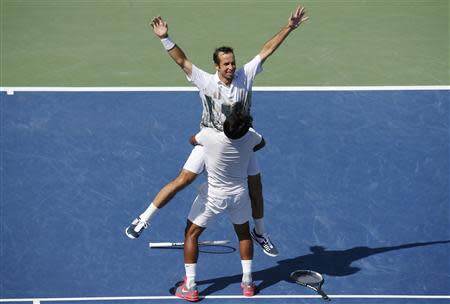 Leander Paes of India lifts playing partner Radek Stepanek of the Czech Republic after they defeated Alexander Peya of Austria and Bruno Soares of Brazil in their men's doubles final match at the U.S. Open tennis championships in New York September 8, 2013. REUTERS/Ray Stubblebine