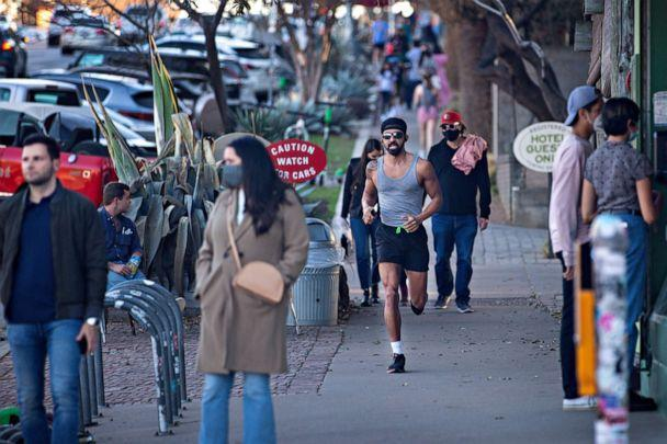 PHOTO: Pedestrians walk down South Congress Ave. on March 3, 2021 in Austin, Texas. Gov. Greg Abbott announced today the state will end its mask mandate and allow businesses to reopen at 100 percent capacity on March 10. (Montinique Monroe/Getty Images)