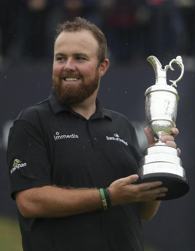 Ireland's Shane Lowry hold up the Claret Jug trophy as he poses for the media and the crowd after winning the British Open Golf Championships at Royal Portrush in Northern Ireland, Sunday, July 21, 2019.(AP Photo/Jon Super)