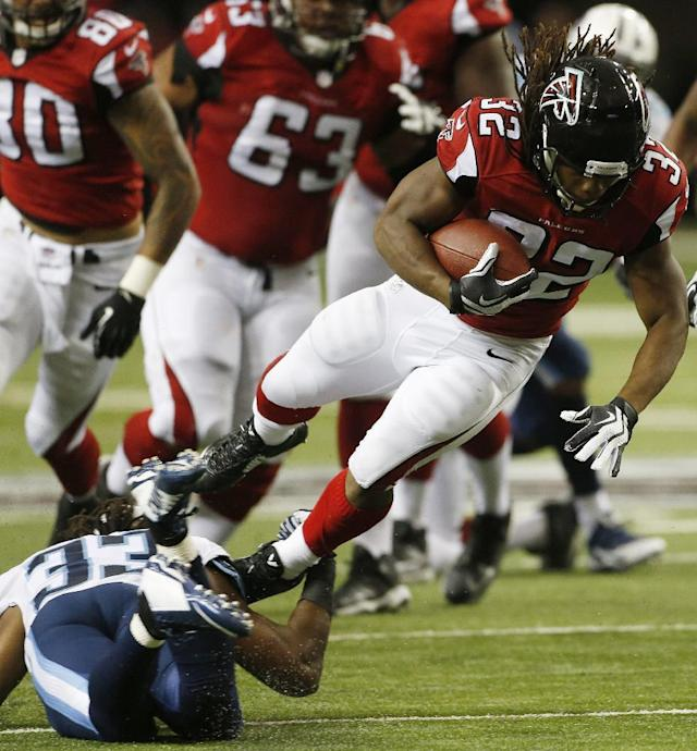 Atlanta Falcons running back Jacquizz Rodgers (32) runs past Tennessee Titans free safety Michael Griffin (33) during the first half of an NFL preseason football game, Saturday, Aug. 23, 2014, in Atlanta. (AP Photo/John Bazemore)