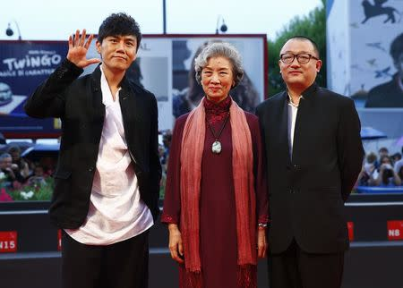 "Director Wang Xiaoshuai poses with cast members Qin Hao and Lu Zhong during the red carpet for the movie ""Chuangru zhe"" (Red amnesia) at the 71st Venice Film Festival"