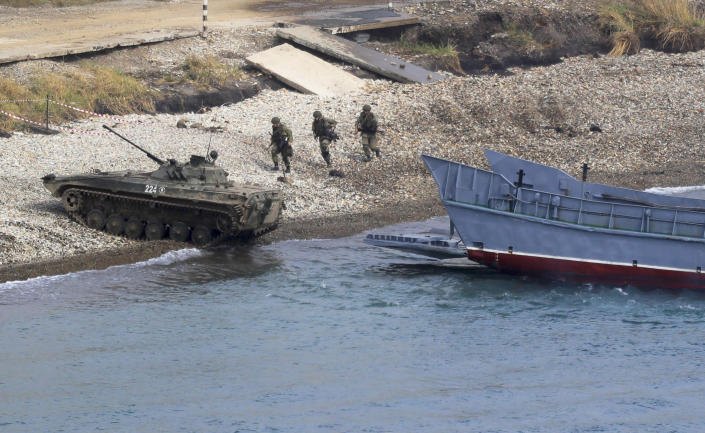 """A Russian navy landing vessel unloads an armored vehicle during Russian military maneuvers Vostok 2018 on the training ground """"Klerk,"""" about 50 kilometers (31 miles) south of Vladivostok, Russian Far East port, Russia, Saturday, Sept. 15, 2018. The weeklong Vostok 2018 maneuvers are the largest war games Russia ever had. (AP Photo/Sergei Grits)"""