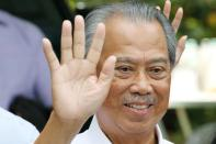 Malaysia's Prime Minister Designate and former interior minister Muhyiddin Yassin waves to reporters outside his residence in Kuala Lumpur