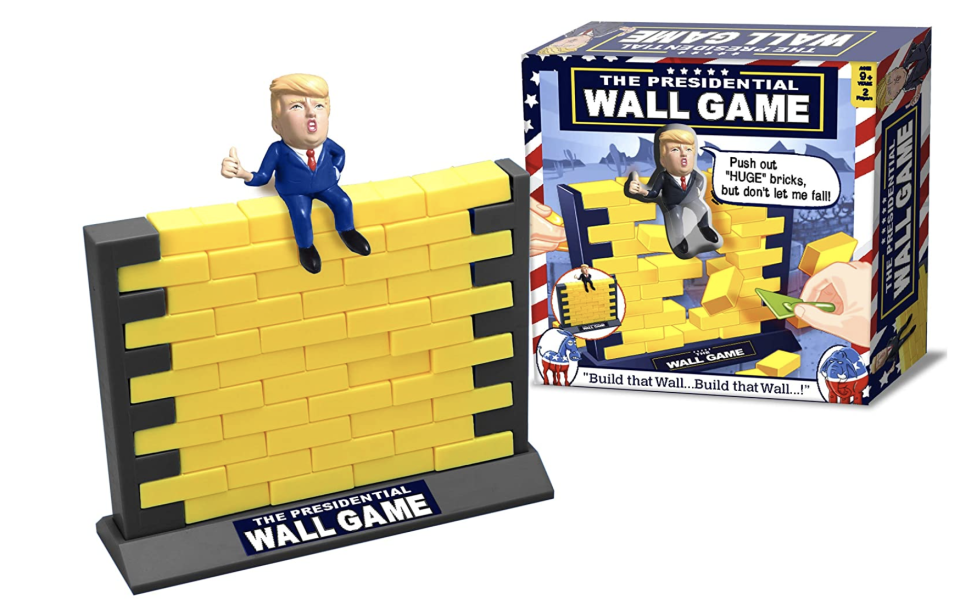 A Trump character sits atop a plastic wall made of little yellow bricks