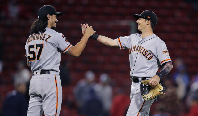 San Francisco Giants relief pitcher Dereck Rodriguez (57) and left fielder Mike Yastrzemski, right, celebrate after the Giants defeated the Boston Red Sox in 15 innings during a baseball game at Fenway Park in Boston, early Wednesday, Sept. 18, 2019. Yastrzemski homered and Rodriguez got the win in the 7-6 victory. (AP Photo/Charles Krupa)