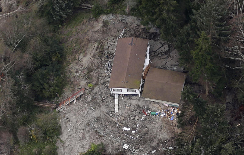 In this aerial photo, a house sits near the bottom edge of a landslide near Coupeville, Wash. on Whidbey Island, Wednesday, March 27, 2013. The slide severely damaged one home and isolated or threatened more than 30 on the island, about 50 miles north of Seattle in Puget Sound. No one was reported injured in the slide, which happened at about 4 a.m. Wednesday. (AP Photo/Ted S. Warren)