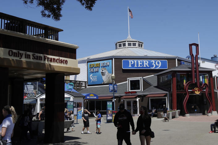 FILE - In this June 18, 2020, file photo, people visit Pier 39 during the coronavirus outbreak in San Francisco. San Francisco is poised to allow indoor dining, movie theaters and gyms with reduced capacity as the rate of coronavirus cases and deaths improve, allowing more of California's economy throughout the state to open back up for business. It's unclear which activities might open when. Mayor London Breed is scheduled to provide an update at the tourist-friendly Pier 39 in Fisherman's Wharf Tuesday, March 2, 2021. (AP Photo/Jeff Chiu, File)