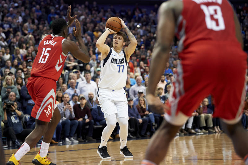 Dallas Mavericks forward Luka Doncic (77) shoots a 3-pointer over Houston Rockets center Clint Capela (15) during the second half of an NBA basketball game, Saturday, Dec. 8, 2018, in Dallas. (AP Photo/Cooper Neill)