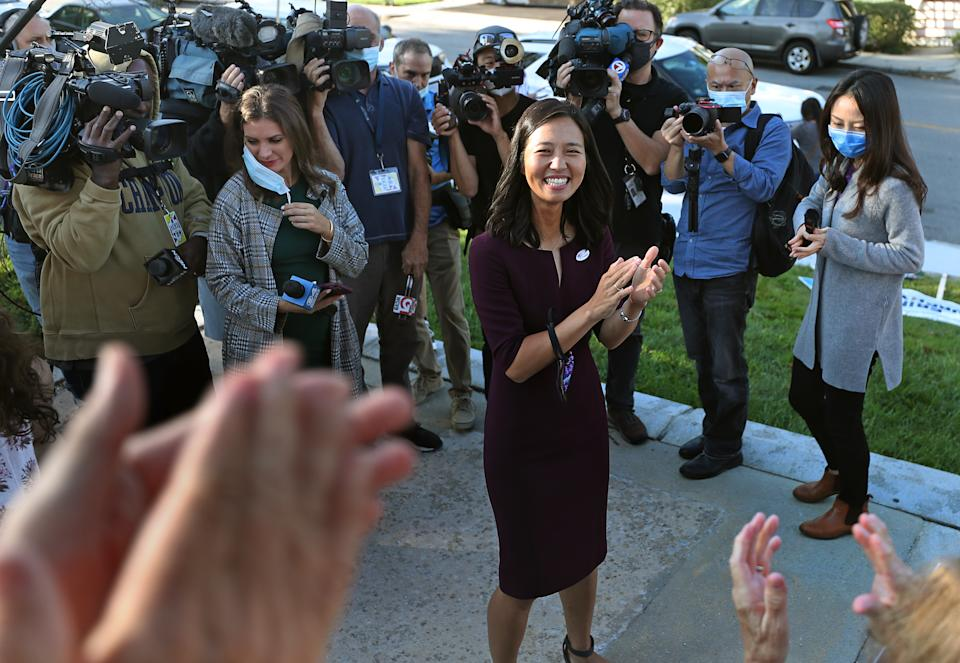 Michelle Wu stands in front of people with cameras, microphones and press badges while smiling and clapping with supporters, whose hands are visible in the foreground.