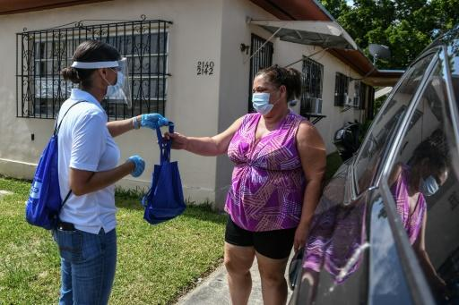 Cathy Burgos (L) leads a team that delivers supplies to counter the spread of the novel coronavirus in Miami