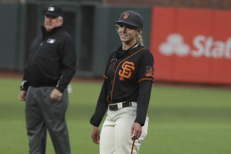 San Francisco Giants first base coach Alyssa Nakken smiles during an exhibition baseball game against the Oakland Athletics in San Francisco, Tuesday, July 21, 2020. (AP Photo/Jeff Chiu)