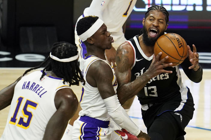 Los Angeles Clippers guard Paul George (13) is defended by Los Angeles Lakers guard Dennis Schroeder, center, during the first half of an NBA basketball game Sunday, April 4, 2021, in Los Angeles. (AP Photo/Marcio Jose Sanchez)