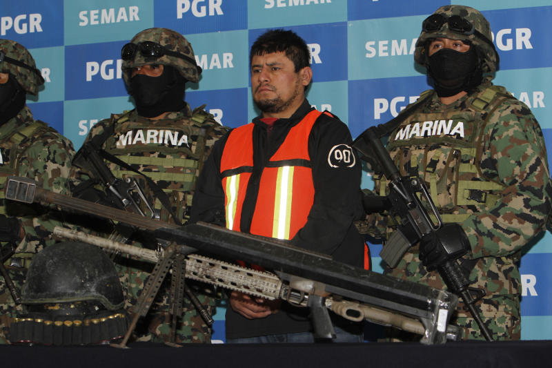 """Raul Lucio Fernandez Lechuga, alias """"Lucky,"""" center, stands behind a seized arsenal while presented to the press under the custody of navy marines at the Organized Crime Special Investigations Unit (SIEDO) headquarters in Mexico City, Tuesday Dec. 13, 2011.  According to federal authorities, Fernandez is one of the most wanted criminals in Mexico and the U.S., and is allegedly a top regional leader of the Zetas criminal organization, as well as a founding member of the Zetas.  The federal government had offered a 15 million-peso reward, about $1.2 million, for information leading to his arrest. The Zetas organization was formed by a small group of elite soldiers based in Tamaulipas state, across the border from Texas, who deserted to work for the Gulf drug cartel in the 1990s.  (AP Photo/Marco Ugarte)"""