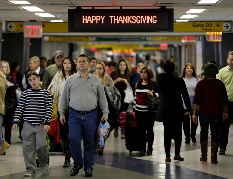 "Travelers walk under a sign reading ""Happy Thanksgiving"" at LaGuardia Airport in New York, Tuesday, Nov. 26, 2013. A winter storm system that hit parts of Arkansas, Oklahoma and Texas swept toward the densely populated East Coast on Tuesday, threatening to disrupt the plans of travelers ahead of the long Thanksgiving holiday weekend. (AP Photo/Seth Wenig)"