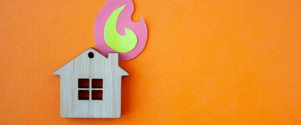 Fire house, insurance and mortgage concept. Small wooden house toy and paper fire shape on orange background top view with copy space