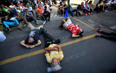Scores of Central American migrants rest in front of the office of the United Nation's human rights body in Mexico City - Credit: AP
