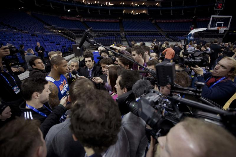 """New York Knicks forward Carmelo Anthony, at left, is surrounded by members of the media as he speaks before the start of a training session at the 02 arena in London, Wednesday, Jan. 16, 2013. The Detroit Pistons are due to play a """"home"""" NBA league game against the New York Knicks at the arena on Thursday. (AP Photo/Matt Dunham)"""