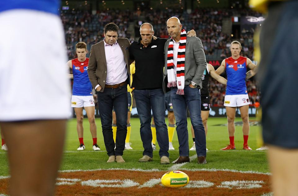 Garry Lyon, Tony Lockett and Stewart Loewe pause to remember Danny Frawley during the 2021 AFL Round 02 match between the St Kilda Saints and the Melbourne Demons at Marvel Stadium on March 27, 2021 in Melbourne, Australia.