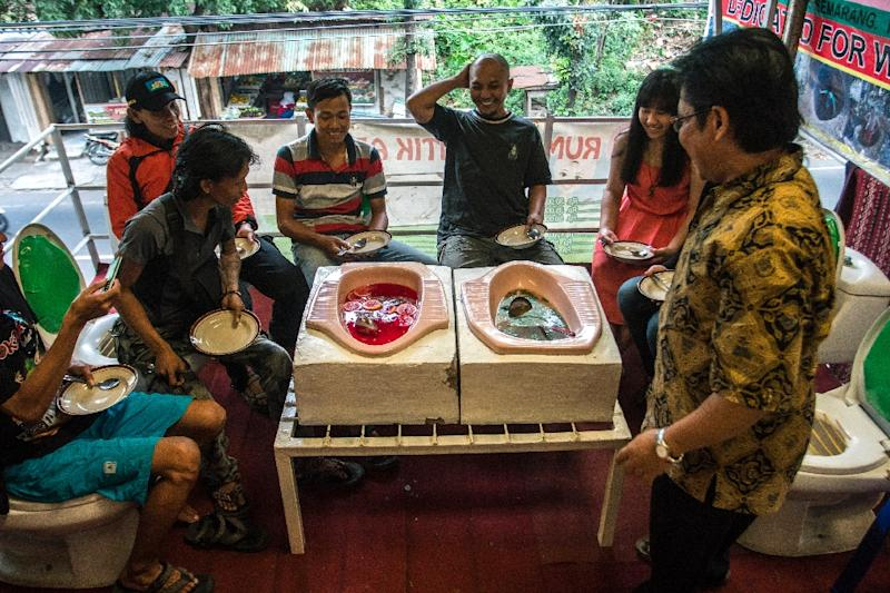 Customers enjoy a meal at the 'Jamban Cafe' in the city of Semarang on Indonesia's Java island, a small eatery where a handful of diners sit on upright toilets around a table where food is served in two squat toilets (AFP Photo/Suryo Wibowo)