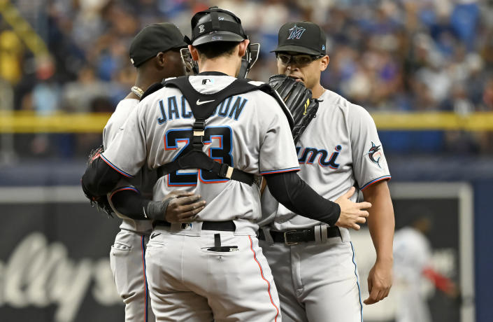 Miami Marlins catcher Alex Jackson (23) and shortstop Jazz Chisholm Jr., left, talk with starter Jesus Luzardo, right, on the mound during the first inning of a baseball game against the Tampa Bay Rays, Sunday, Sept. 26, 2021, in St. Petersburg, Fla. (AP Photo/Steve Nesius)