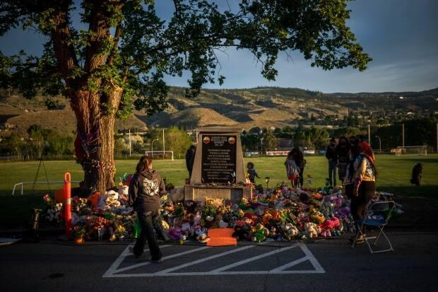 The sun sets on a makeshift memorial outside the former Kamloops Indian Residential School to honour the 215 children whose remains were reported to be found buried in Kamloops, British Columbia. (Ben Nelms/CBC - image credit)