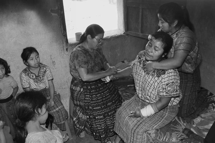 <p>Berta Navichoc heals Marta Mendoza Damian after she fell from a truck on her way to work. (Photograph by Fran Antmann) </p>