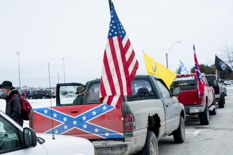 Student demonstrators park trucks bearing Confederate flags and other banners and signs along the outer drive of Bay City Western High School in support of a Bay City Western High School student, who claims his Confederate flag was torn from his truck last week, Wednesday, April 18 2018, in Auburn, Mich. (Jacob Hamilton/The Bay City Times via AP)