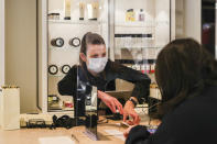 A retail worker wearing a face mask serves a customer behind a shield as she processes a sale at a large retail department store in Melbourne, Australia, Wednesday, Oct. 28, 2020. Australia's second largest city of Melbourne which was a coronavirus hotspot emerges from a nearly four-months lockdown, with restaurants, cafes and bars opening and outdoor contact sports resuming on Wednesday. (AP Photo/Asanka Brendon Ratnayake)