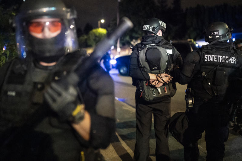 PORTLAND, OR - AUGUST 30: An Oregon State Trooper arrests journalist Gabriel Trumbly during a crowd dispersal near the Portland east police precinct on August 30, 2020 in Portland, Oregon. City leaders asked for calm and time to conduct an investigation after a man was shot and killed near a pro-Trump rally on Saturday. (Photo by Nathan Howard/Getty Images)