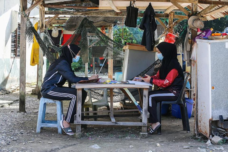 Nur Alea Soffiyyah Ahmad Hanif (left) and her schoolmate Hanis Syuhada Razali (right) attend online classes in front of their house on Pulau Aman January 22, 2021. — Picture by Sayuti Zainudin