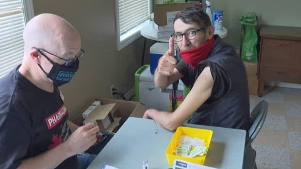 Robert Morgan of Saint John, right, was happy to get his second COVID-19 vaccine from pharmacist Jason Steeves at a pop-up clinic being offered at the Crescent Valley Resource Centre in the city's north end Thursday. 'Goodbye COVID,' he said. (Gary Moore/CBC - image credit)