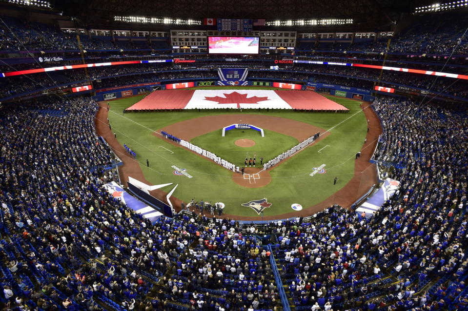 FILE - Members of the Toronto Blue Jays and the Detroit Tigers lineup before an opening day baseball game at Rogers Centre in Toronto, in this Thursday, March 28, 2019, file photo. Talks between the Toronto Blue Jays and the Canadian government have accelerated significantly and an exemption on border restrictions that would allow them to play in Canada starting July 30 may be possible, an official familiar with the talks told The Associated Press on Friday, July 16, 2021. (Frank Gunn/The Canadian Press via AP, File)