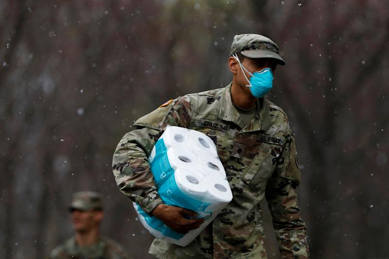 A member of Joint Task Force 2, composed of soldiers and airmen from the New York Army and Air National Guard, wears a face mask while carrying paper towels as he arrives to sanitize and disinfect the Young Israel of New Rochelle synagogue, as snow falls during the coronavirus disease (COVID-19) outbreak in New Rochelle, New York, U.S., March 23, 2020. REUTERS/Andrew Kelly TPX IMAGES OF THE DAY