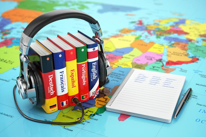 Foreign-language books clamped between a pair of headphones and resting on a world map, with a notebook and pen beside them.