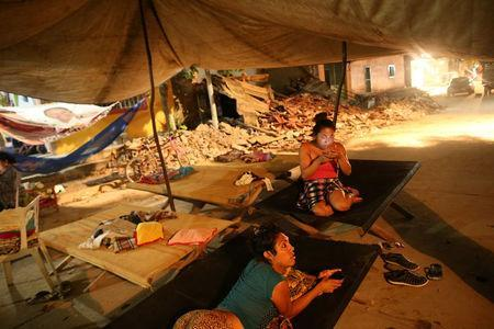 Ximena, 26 and Peregrina, 26, indigenous Zapotec transgender women also knows as Muxe, rest on a street after an earthquake that struck on the southern coast of Mexico late on Thursday, in Juchitan, Mexico, September 10, 2017. REUTERS/Edgard Garrido