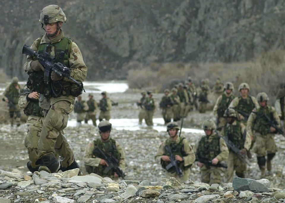 """<span class=""""caption"""">Long time there: U.S. troops maneuver around the central part of the Baghran river valley as they search for remnants of Taliban and al-Qaida forces on Feb. 24, 2003. </span> <span class=""""attribution""""><a class=""""link rapid-noclick-resp"""" href=""""https://newsroom.ap.org/detail/AFGHANISTANUSOPERATIONVIPER/d38e6cd3d2e0da11af9f0014c2589dfb/photo?Query=U.S.%20troops%20afghanistan&mediaType=photo&sortBy=arrivaldatetime:asc&dateRange=Anytime&totalCount=3217&currentItemNo=43"""" rel=""""nofollow noopener"""" target=""""_blank"""" data-ylk=""""slk:Aaron Favila/Pool/AP Photo"""">Aaron Favila/Pool/AP Photo</a></span>"""