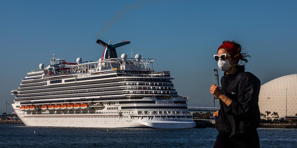 A woman wearing a face mask runs with cruise ships docked in the background due to a no-sail order at the port of Long Beach, California, on April 11, 2020.
