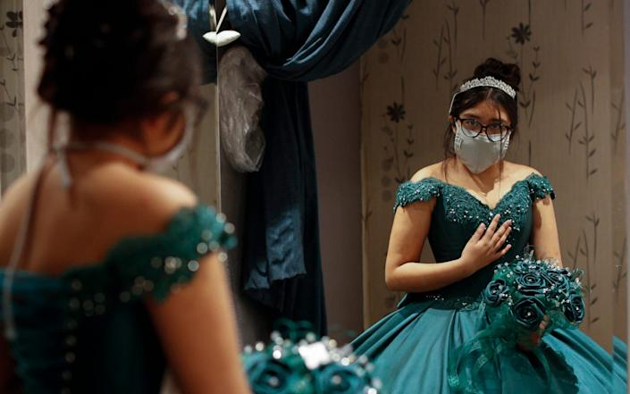 Ximena Canejo Hernandez checks her reflection in a mirror as she tries on her chosen Quinceanera dress - Rebecca Blackwell / AP