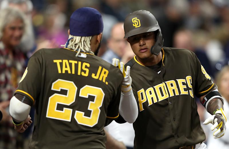 SAN DIEGO, CALIFORNIA - JULY 12: Manny Machado #13 is congratulated by Fernando Tatis Jr. #23 of the San Diego Padres after hitting a solo homerun during the sixth inning of a game against the Atlanta Braves at PETCO Park on July 12, 2019 in San Diego, California. (Photo by Sean M. Haffey/Getty Images)