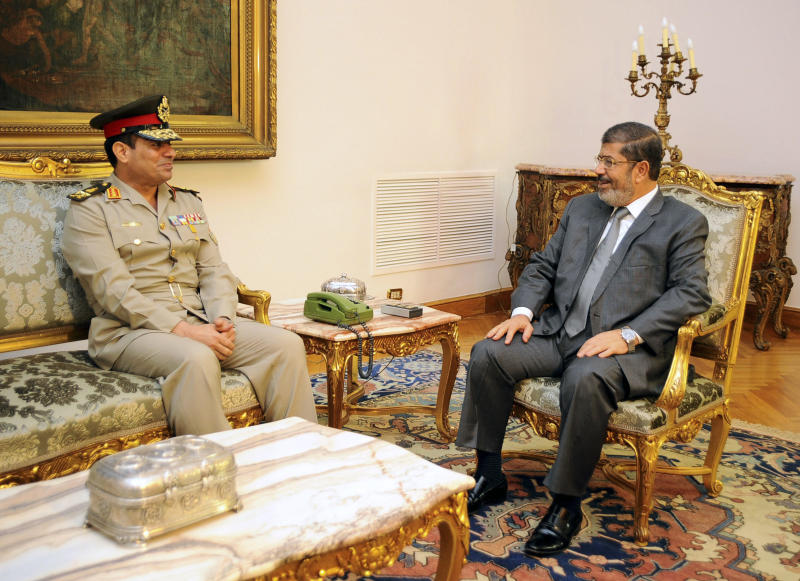 FILE - In this Monday, Aug. 13, 2012 file photo, Egyptian Minister of Defense, Lt. Gen. Abdel-Fattah el-Sissi, left, meets with Egyptian President Mohammed Morsi in Cairo, Egypt. Thousands of mourners chanting for the downfall of Egypt's president marched in funerals again Tuesday in the restive city of Port Said as the army chief warned the state could collapse if the latest political crisis drags on. (AP Photo/Egyptian Presidency, File)