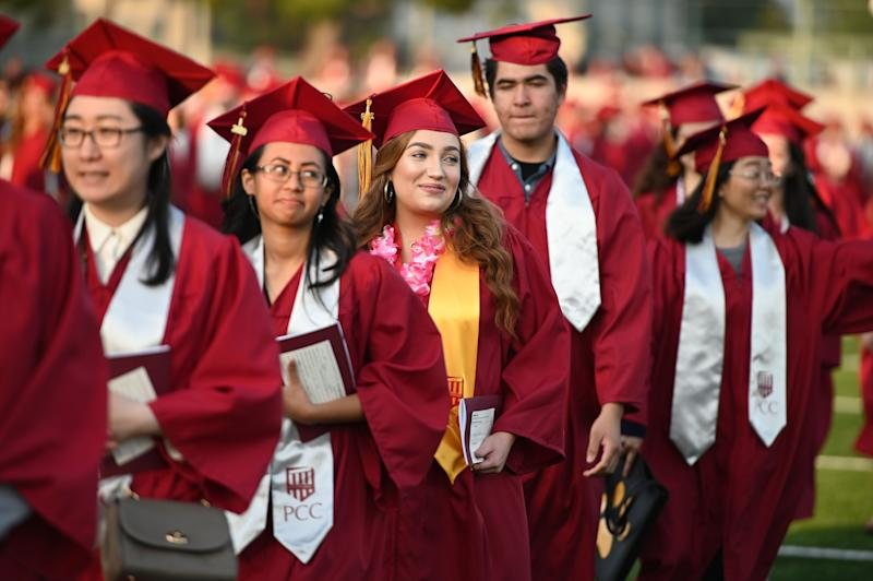 Haley Walters (C) marches with her class at the Pasadena City College graduation ceremony, June 14, 2019, in Pasadena, California. - Haley Walters is five years shy of earning a law degree and, if everything goes according to plan, she should be indebted for $100,000 by the time she enters the work force. Like millions of Americans, Walters, 19, is paying a steep price for an education that will weigh her down financially for much of her adult life. (Photo by Robyn Beck / AFP) (Photo credit should read ROBYN BECK/AFP via Getty Images)
