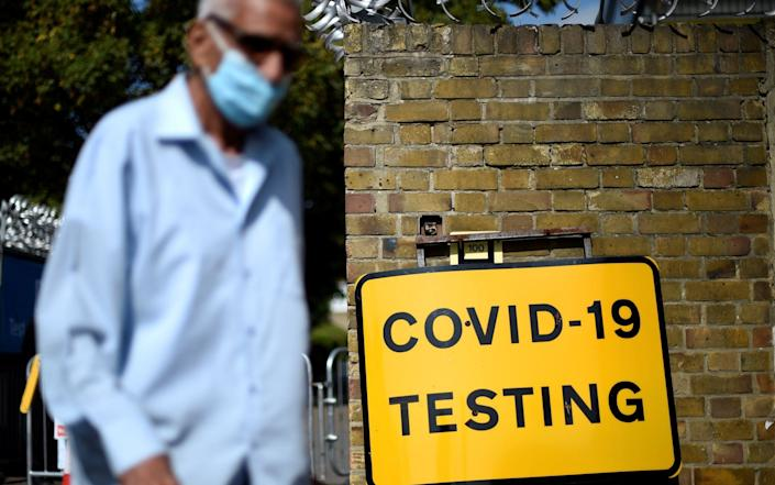 A man wearing a face covering due to the COVID-19 pandemic, waks past a sign outside a novel coronavirus walk-in testing centre in East Ham in east London -  DANIEL LEAL-OLIVAS  /AFP