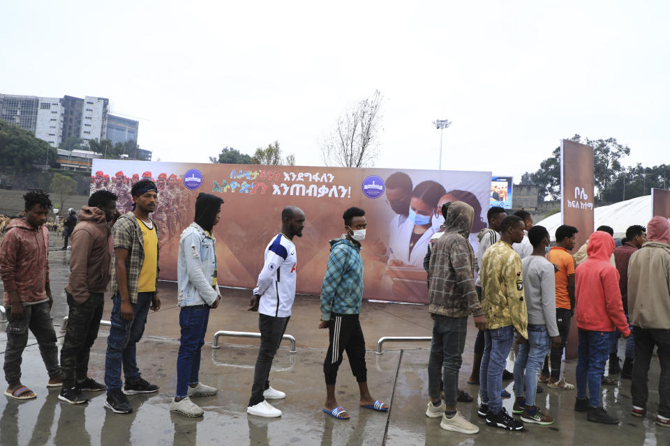 People joining the Defense Forces queue, at Meskel Square, in Addis Ababa, Ethiopia, Tuesday, July 27 2021. A repatriation program is underway for young people from Ethiopia who have decided to join the Defense Forces. (AP Photo)