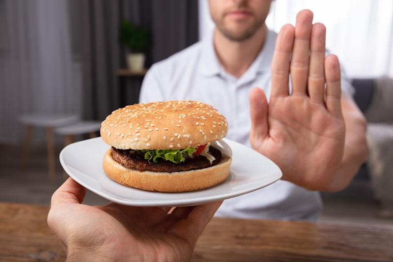 A Close-up Of A Man's Hand Refusing Burger on a white plate Offered By Person